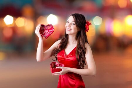 Portrait of beautiful young lady with heart shaped present box photo