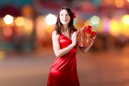 Portrait of beautiful young woman with red heart shaped present box happy smiling and happy looking up on bokeh lights background photo