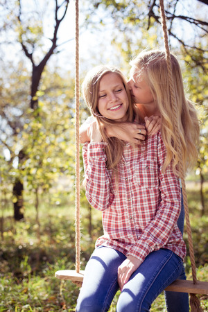 Two happy teenage girls embracing together in autumn park or garden background on bright sunny day photo
