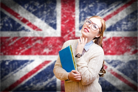 Portrait of young pretty lady in glasses holding books with the UK flag on the background.