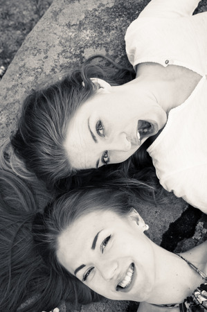 Closeup black and white picture of pretty girl friends relaxing head to head happy smiling photo