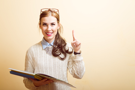 pretty lady: Portrait of beautiful young lady in glasses holding papers or books and pointing up Stock Photo