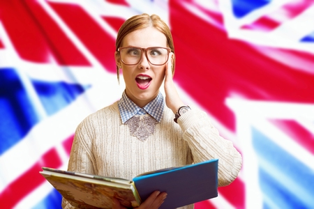 Portrait of funny young pretty female in glasses holding books with the UK flag on the background. Learn English