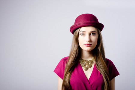 Portrait of elegant beautiful woman in red hat looking at camera, studio shot photo