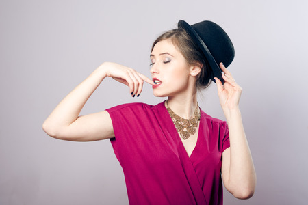 Portrait of elegant beautiful woman in black hat, dreaming with closed eyes, studio shot photo