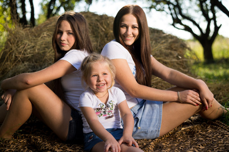 Three happy girls lying on grass on summer haystack background photo