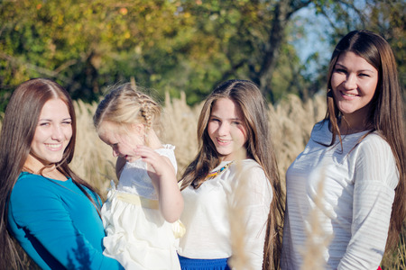 Portrait of four happy female from small kid to adult outdoors photo
