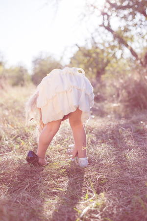 bending down: Little girl on green background looking at the ground or shoes bending down