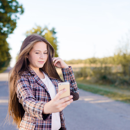 Happy girl taking selfie picture with smartphone outdoors or looking in mirror photo