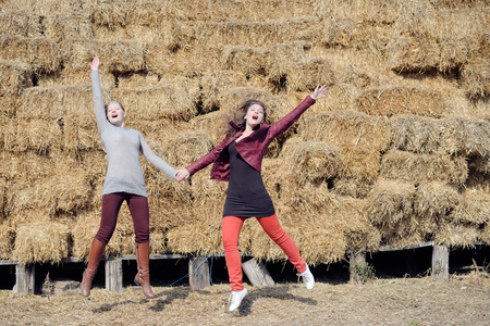 barnyard: Two happy women sisters or friends jumping joyfully having fun at hay stack barnyard outdoors