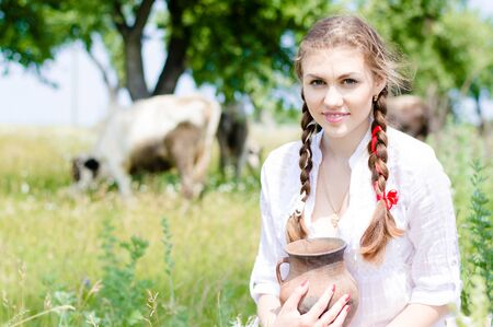 Smiling young farmer carrying bowl of fresh milk photo