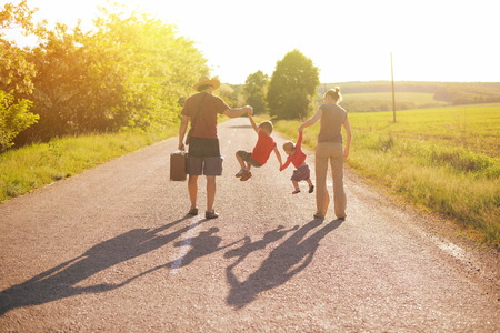 viaje familia: silueta de familia caminando en el parque en la salida del sol