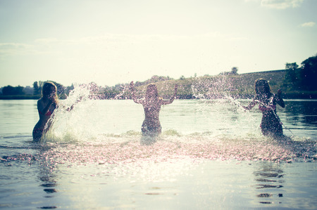 teen girls: Group of happy teen girls playing in water