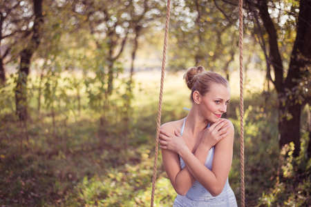 prom dress: Beautiful young woman in prom dress sitting on swing on green summer outdoors