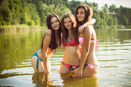 Three beautiful teenage girls in swimsuits standing in water outdoors