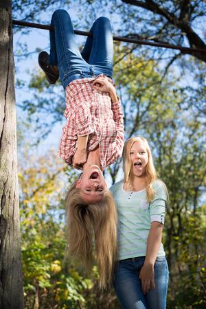 cabeza abajo: Dos adolescentes que se divierten en parque colgando boca abajo en campo verde copia espacio de fondo rural