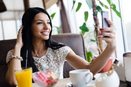 selfy: Portrait of beautiful brunette young lady making selfy picture on mobile cell phone having fun happy smiling on restaurant background