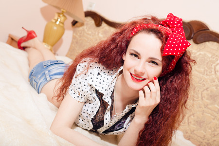 sexi: Picture of sexi young redhead female in shorts with polka dot red ribbon on her head lying on sofa on her belly and looking at camera Stock Photo