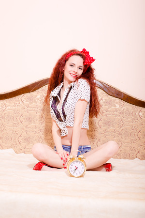 sexi: Picture of sexi young redhead woman with long wavy hair with polka dot red ribbon on her head, sitting on sofa in lotus pose and having fun