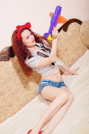 sexi: Funny photo of sexi young redhead woman with long wavy hair in shorts with polka dot red ribbon on head, relaxing on sofa playing with toy plane