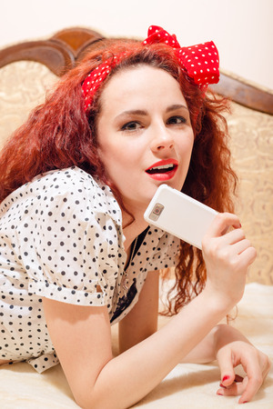 sexi: Closeup portrait of puzzled sexi young redhead woman with long hair and polka dot red ribbon on her head lying on sofa with smart phone & looking at camera
