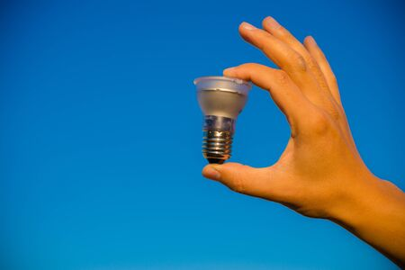 electric bulb: Hand holding LED lamp against bright blue sky copyspace background