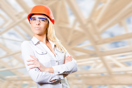 folded hands: Picture of sexi blond business woman with long hair in orange protective helmet and goggles in white buttoned shirt, standing over bokeh background with folded hands Stock Photo