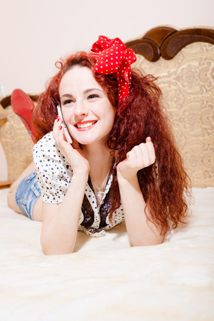 sexi: Sexi beautiful  long-haired young redhead woman with polka dot red ribbon on her head lying on her belly talking on phone looking up