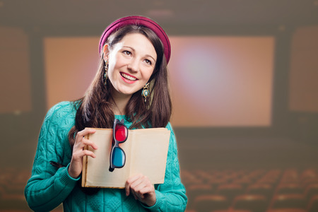 adaptation: Portrait of young joyful brunette girl with 3d glasses and book over cinema background. Film adaptation concept.