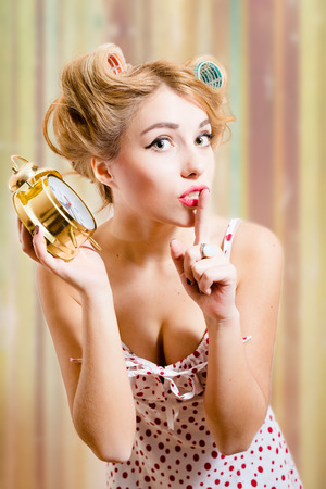 haircurlers: Close up portrait of showing silence sign amazing young blond pinup woman with haircurlers in her hair in dotted langerie holding alarm clock