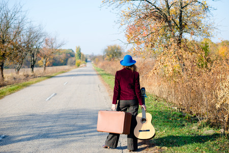 prespective: Young lonely lady in blue hat and red jacket walking away with retro suitcase and guitar along empty rural road on outdoors background