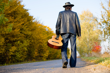 back country: Walking on empty sunny day country road outdoors holding guitar with hand lonely man in leather jacket, jeans and hat