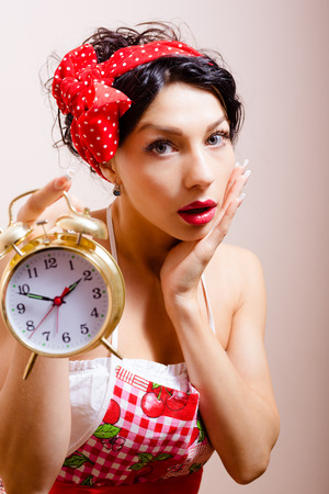 alice band: Young worried pinup lady in red polka dot Alice band and apron holding retro alarm clock, with open mouth and her palm put to her cheek in desbelief looking at camera. Stock Photo