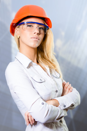 bossy: Closeup picture of young sexy bossy blonde girl in white shirt protective helmet and glasses with folded hands Stock Photo