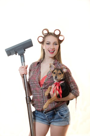 sexi: Isolated picture of sexi funny young blond lady in curlers holding cute doggy and vacuum cleaner