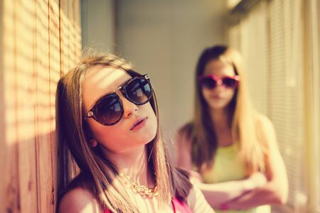 sunroom: Closeup picture of two sad pretty teenage girls wearing sunglasses sitting in sunroom with blinds on sunny day