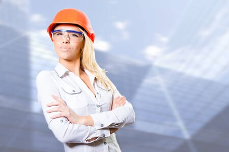 sexi: Closeup portrait of young sexi bossy blonde lady in white shirt protective helmet and glasses with folded hands looking away copyspace over grey background