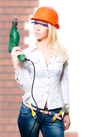 bossy: Closeup picture of young sexi bossy blonde girl in white shirt protective helmet and glasses with drill over brick  background