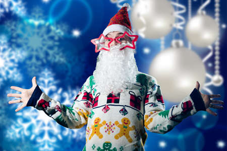 nick: Young man in Santa Claus costume on blue background with Christmas balls