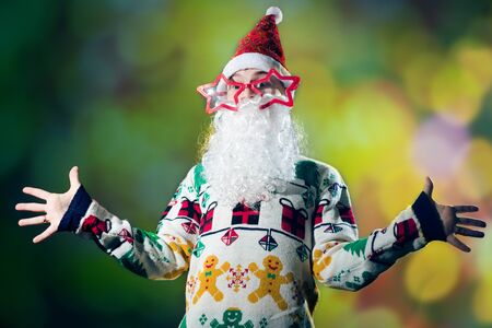 Young man in Santa Claus costume on festival lights background