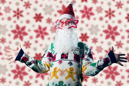 saint nick: Young man in Santa Claus costume on red snowflakes background