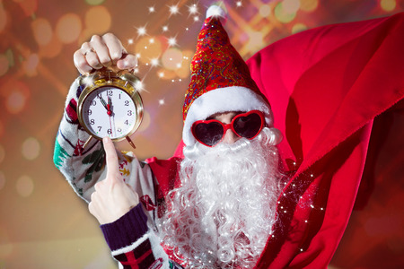 saint nick: Young man in Santa Claus costume and sunglasses pointing on clock on blurred background Stock Photo