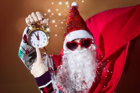st  nick: Young man in Santa Claus costume and sunglasses pointing on clock on blurred background Stock Photo