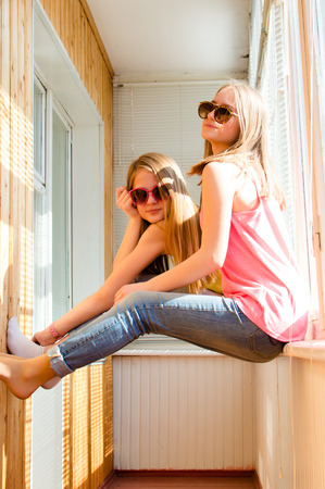 sunroom: Picture of two happy pretty teenage girls in sunglasses having fun in sunroom with blinds on sunny day