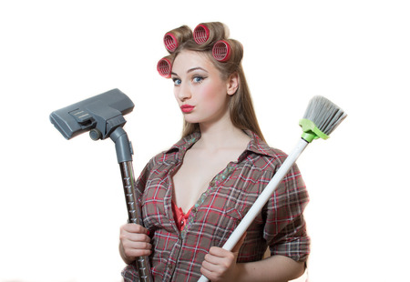 hoover: Isolated picture of pin up lady in curlers standing with hoover and broom looking tired