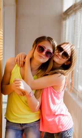 sunroom: Closeup picture of two happy pretty teenage girls wearing sunglasses hugging in sunroom with blinds on sunny day