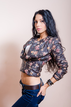 Half length portrait of young pretty brunette lady with long wavy gorgeous  hair in leather jacket and belly top with her hands on her waist
