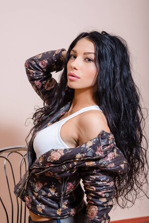 coquete: Young coquette female with beautiful long hair sitting on retro chair in leather jacket with floral pattern on white background Banco de Imagens