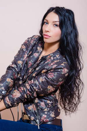 coquette: Young coquette female with beautiful long hair sitting on retro chair in leather jacket with floral pattern on white background Stock Photo
