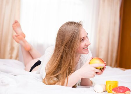 coquette: Young happy smiling coquette  girl in lingerie eating apple lying on her belly in bedroom